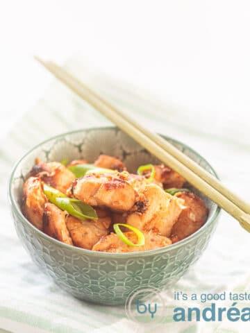 Een groen kommetje met kip met 4 smaken gekruid. Twee chopsticks liggen erboven op. Het kommetje staat op een groen wit gestreepte handdoek
