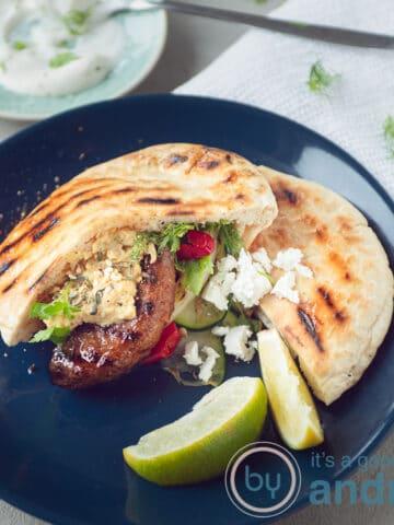 een vierkante foto met een blauw bord met daarop een pita broodje met runderhamburger en gegrilde groenten