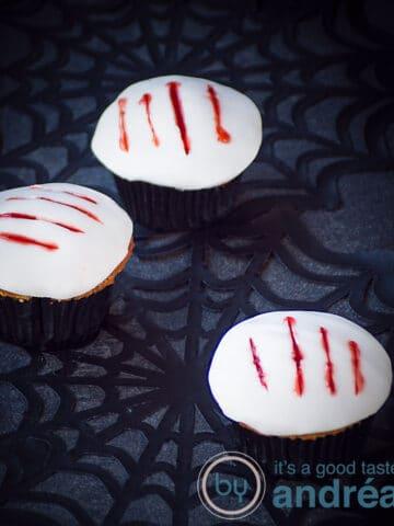 Drie cupcakes met een witte toplaag en vier klauw afdrukken gevuld met aardbeien bloed. Ze zijn geplaatst op een spinnenweb.