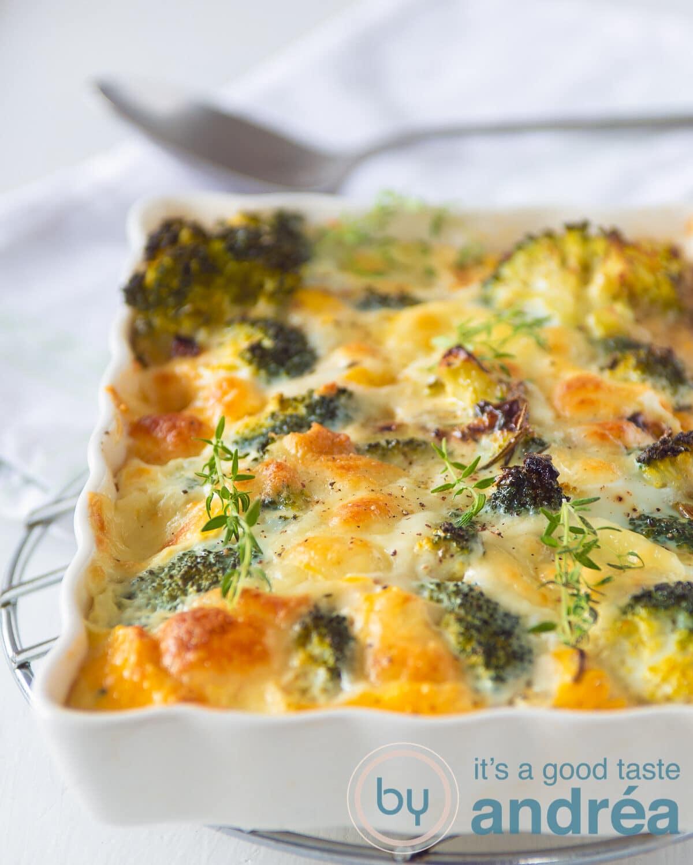 Een witte ovenschaal gevuld met eieren, broccoli en mozzarella gebakken in de oven. Een lepel op de achtergrond