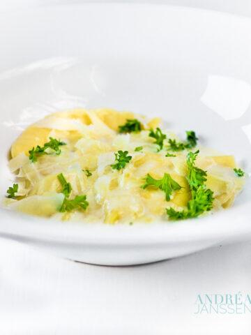 Ravioli gevuld met kaas in een wit diep bord