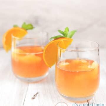 2 glazen met oranje cocktail en een schijfje sinaasappel