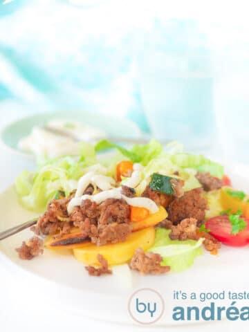 Een wit bord met aardappeltjes, gehakt, ijsbergsla gegarneerd met tomaat en knoflooksaus