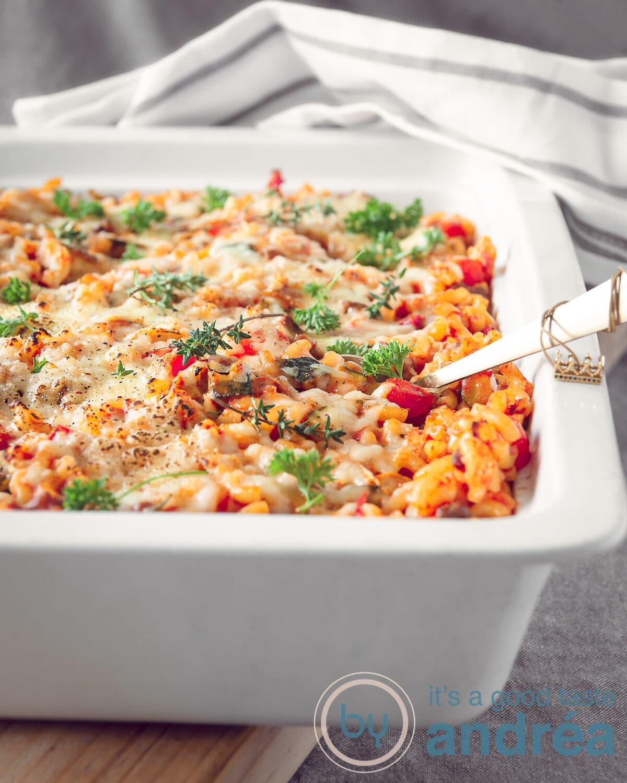 Een witte ovenschaal gevuld met macaroni, kaas, mascarpone en tomatensaus en lekkere groenten. Een wit grijze handdoek licht op de achtergrond