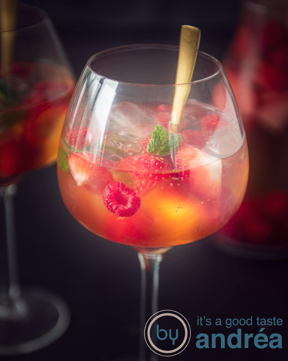 A glass filled with white sangria 43 on a black background. A jar and another glass are in the background