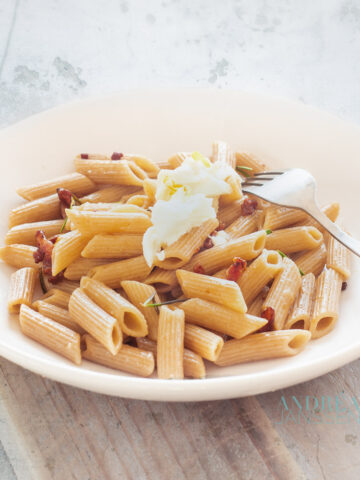 een wit bord met Spelt penne met rozemarijn, spekjes en citroen en getopt met mozzarella