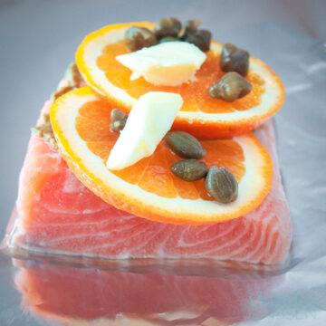 aluminiumfolie daarop zalm met een schijfje sinaasappel, boter en kappertjes