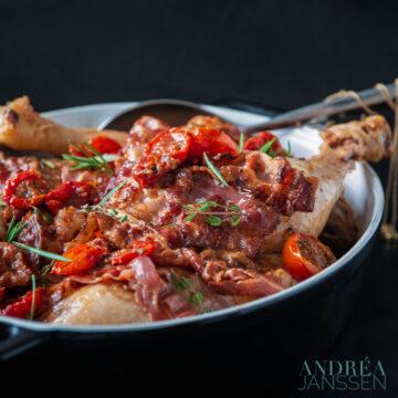 kippenpoten in een zwarte ovenschaal met bacon en tomaat