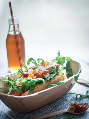 een bamboe bakje met een Hot dog de luxe en een flesje prik