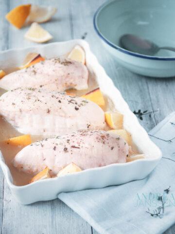 Een ovenschotel schaal met kip, citroen een blauwe kom en een witte doek