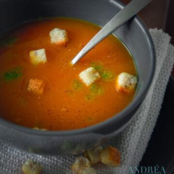 Een kom met pompoensoep, bieslook olie en croutons