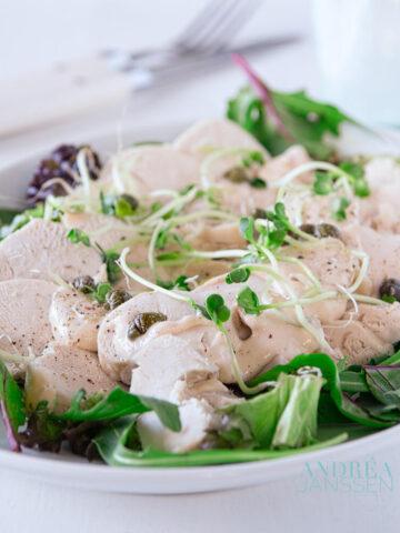delicious turkey vitello tomato on a white plate with green salad