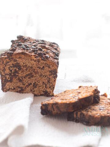 een half krenten en cranberry brood met losse plakjes op een wit doek