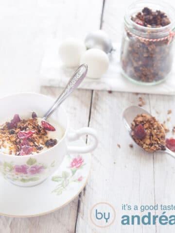 Een kopje gevuld met muesli, cranberries. Kerstballen en een potje met granola in de achtergrond. Een lepel met granola in de rechterkant.