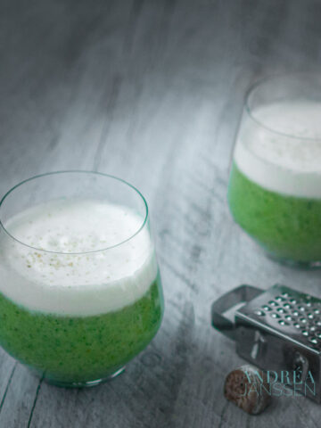 twee glazen gevuld met broccoli soep met een kruidige slagroom topping