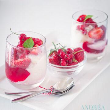 2 glaasjes met frozen yoghurt jam en rood fruit garnering en een bakje rood fruit.