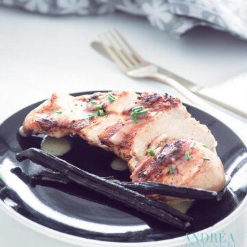 Een zwart bord met kip met vanille-saus