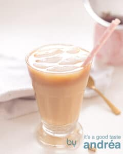 A glass filled with a creamy latte iced coffee with Chai spices. In the background a white cloth and a golden spoon.