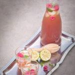 een dienblad met een karaf Limoen rozen ijsthee met verse frambozen en twee glazen gevuld met ijsthee