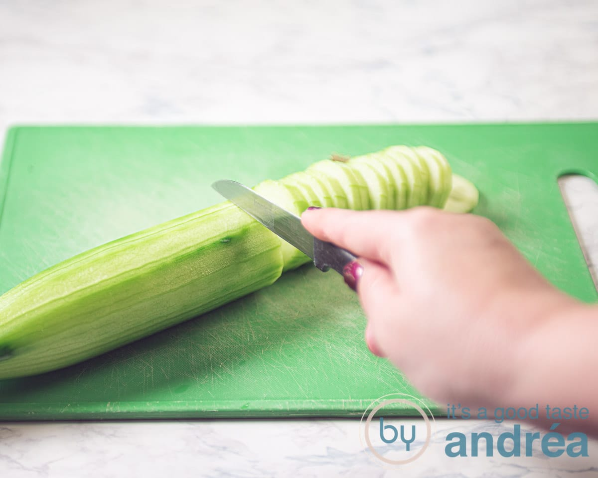 Snij een geschilde komkommer in plakjes