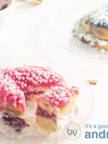 een donut versierd met roze muisjes en een halve donut versierd met blauwe muisjes
