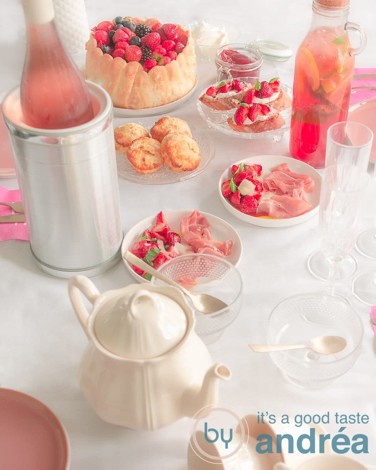 a table with recipes for a summer high tea with strawberries, including a tea pot, wine and lots of strawberreis