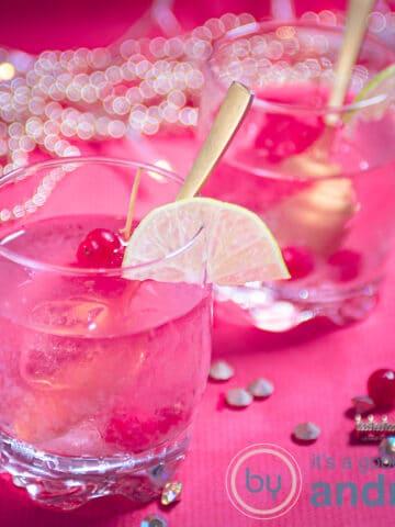 twee glazen caipirinha met rode bessen op een roze ondergrond