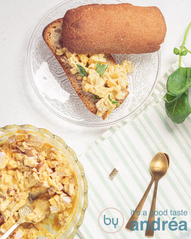 Een broodje met gerookte kip salade, een schaal met salade en basilicum van bovenaf gefotografeerd. Ook een kom met salade is aanwezig