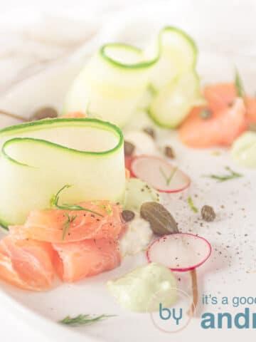 vierkante foto met gerookte zalm, komkommer, en garnering