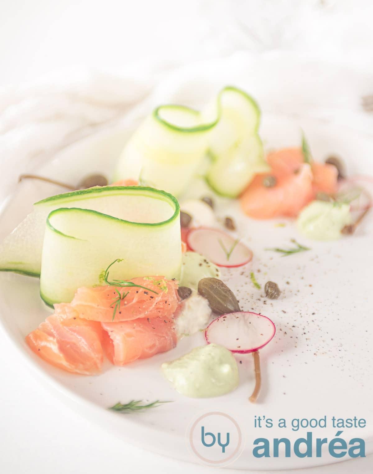 Een wit bord met rolletjes gerookte zalm, komkommer linten en garnering