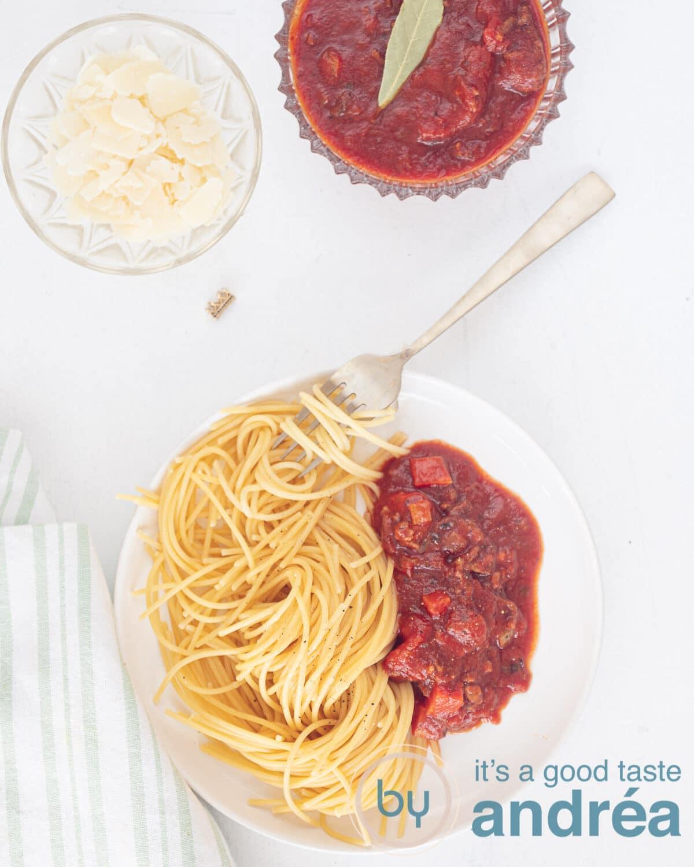 een bord met spaghetti en pastasaus van bovenaf