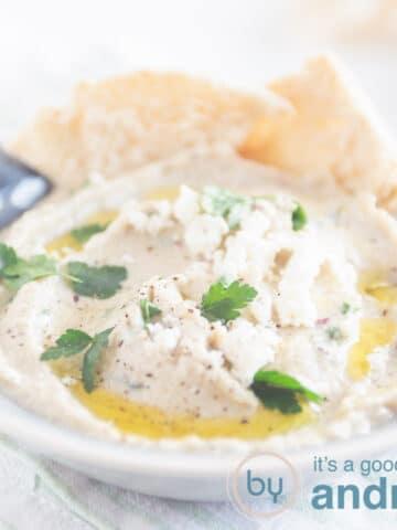 een vierkante foto met een grijs schaaltje, melitzanosalata met peterselie en olijfolie, puntjes pita brood