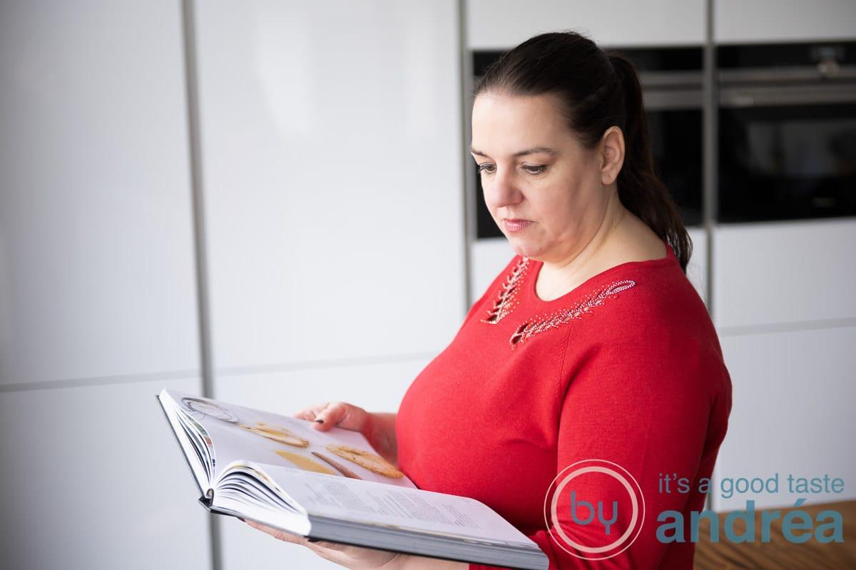 Andrea kijkt in een kookboek