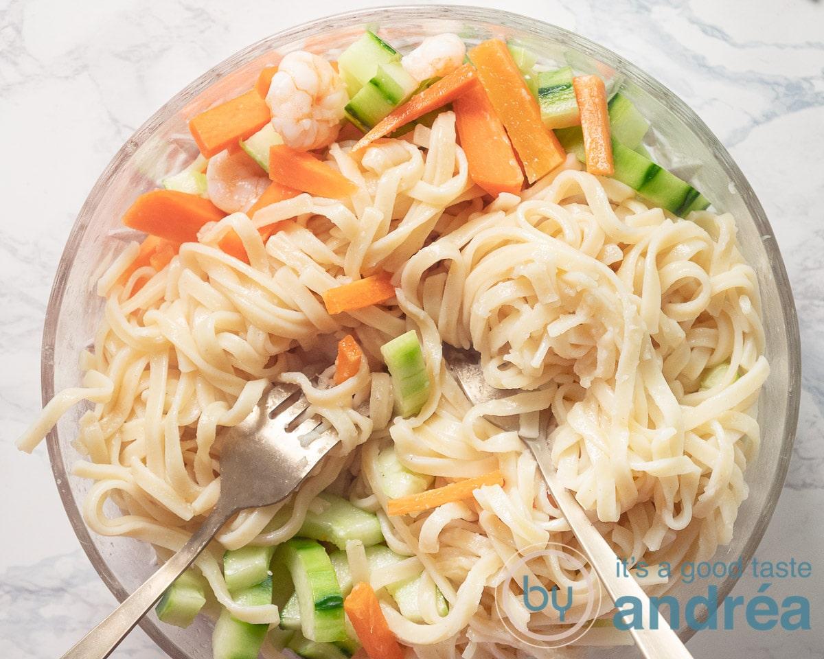Stirring the bami noodles through the vegetables and shrimp salad
