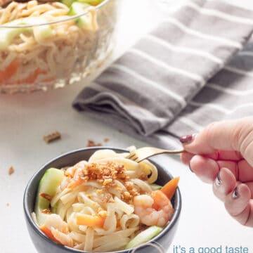 een vork die een beetje van de noedelsalade in een grote kom neemt. Een grote kom gevuld met salade en een grijze handdoek staan achterin