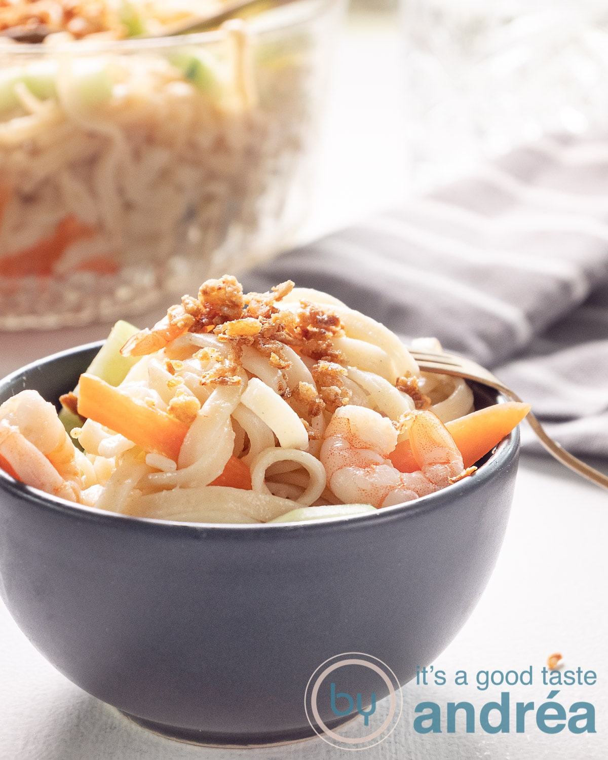 A grey bowl filled with Indonesian noodle salad with cucumber, carrot and shrimp. A glass bowl at the back. A grey towel on the right