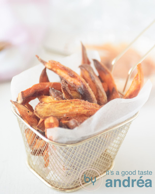 In het midden een gouden frietbakje waarin een bakpapier is gevouwen met friet van zoete aardappels erin