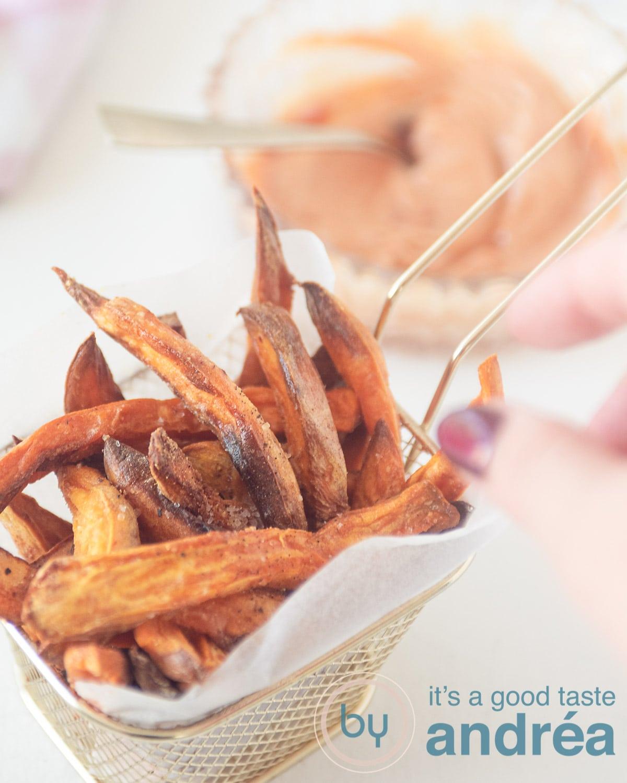 Een hand die een zoet aardappelfrietje uit een gouden frietbakje met bakpapier pakt (en die is gevuld met frietjes) op de achtergrond een dipsaus