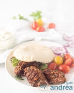 Een wit bord met een pita broodje gevuld met cevapi, sla en tomaatjes. Wat groente ligt er om het bord
