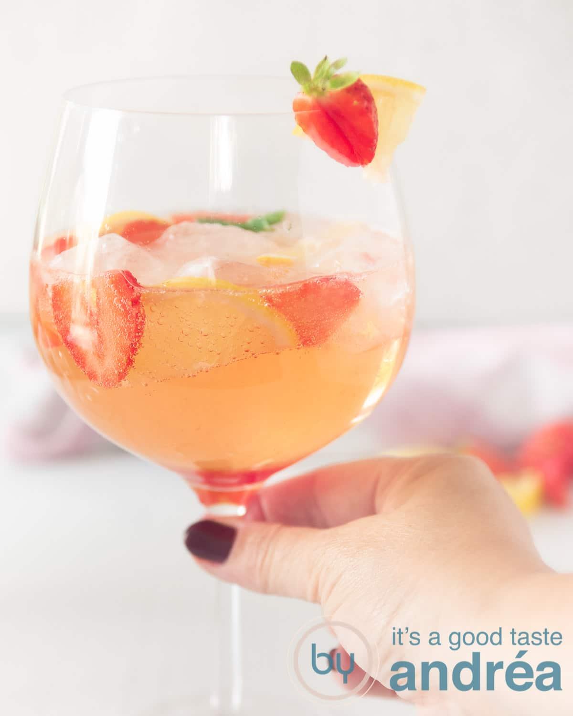 Een hand die een glas strawberry gin cocktail vast pakt met een garnering van aardbei en citroen