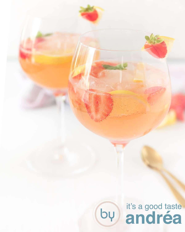Twee glazen gevuld met een gin cocktail van aardbeien achter elkaar. Twee gouden lepels aan de zijkant.